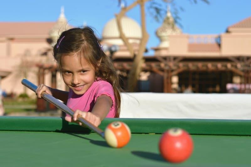 girl playing on mini pool table for kids