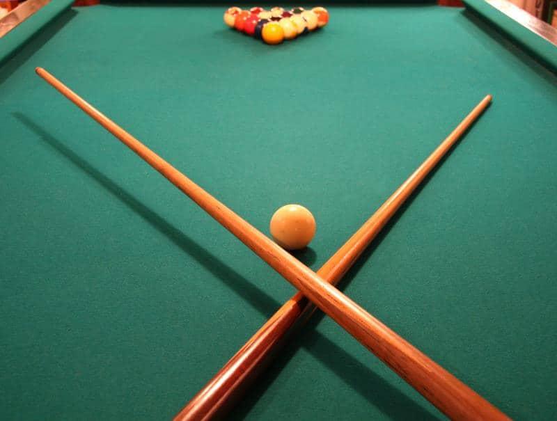 pool sticks on a table with billiard balls